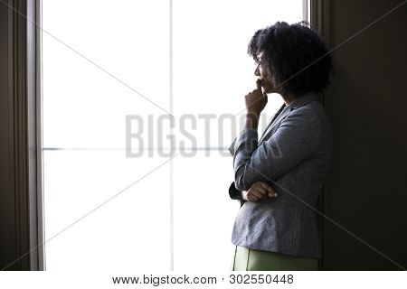 Silhouette Of A Black African American Businesswoman Thinking By The Office Window. She Is Brainstor