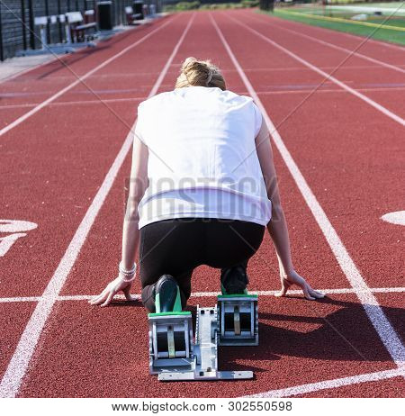 The View From Behind The Starting Blocks Of A High School Female Sprinter Ready To Run Down The Trac