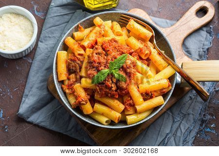 Delicious Rigatoni Pasta With Italian Tomato Meat Ragu Sauce Served In A Pan On Dark Brown Backgroun