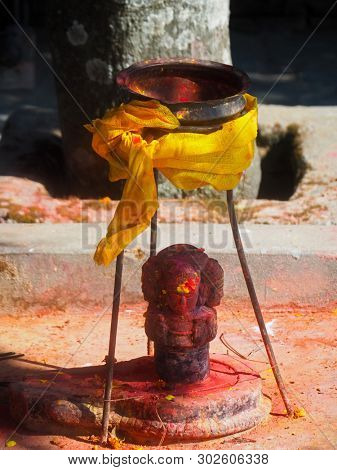 Shrine covered in vermillion to worship Goddess Kali. Red pigment powder on statue, part of Kali Shrine on the mountain in Dhulikhel, Nepal