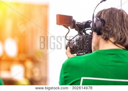 The Concept Of The Creation Of Tv, Video Content, Backstage. A Professional Cameraman Is Filming On