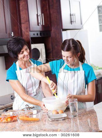 mother teaching teen daughter baking in kitchen