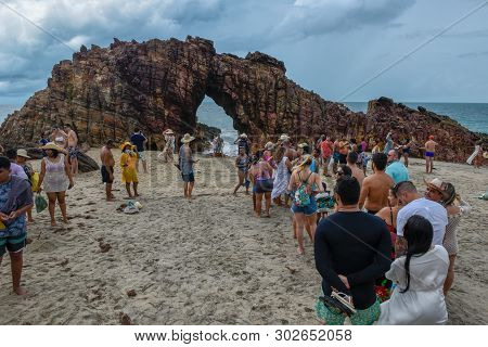 People In Line To Take A Souvenir Photo In Front Of The Natural Arch Of Jericoacoara On Brazil.