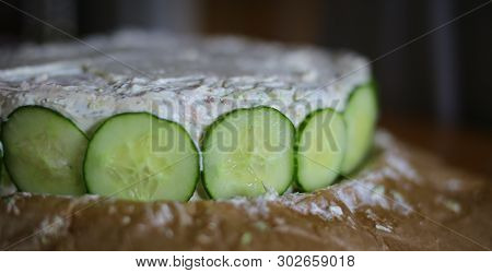 Preparation Of Smorgastarta, A Typical Swedish Dish, With Cucumber Slices.