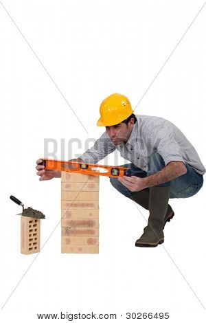 A mason checking a brick pile with his level.