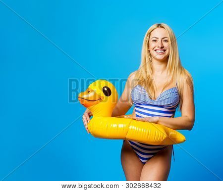 Picture of young blonde in striped swimsuit with life preserver at waist on empty blue background