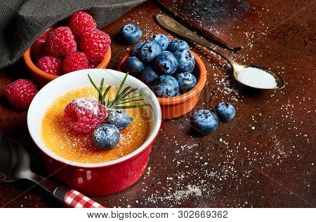 Creme Brulee (cream Brulee, Burnt Cream) With Raspberry And Blueberry Powdered With Sugar On Dark Ru