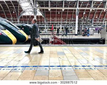 PADDINGTON, LONDON - MAY 20, 2019: Passengers walking inside Paddington train station, a major railway terminus for journeys to and from the West, in London, UK.