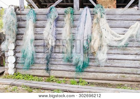 Six Fishing Nets Are Dried On A Log Wall, Located On A Peasant Farmstead.