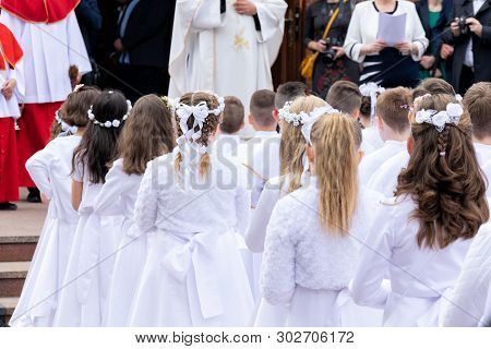 A Group Of Children In Solemn White Clothes Is Waiting In Front Of The Entrance To The Church. Prepa