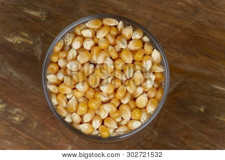 Corn Popcorn In Glass Pot With A Wooden Background