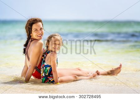 Young mother and little daughter sitting on the beach in Dominican Republic
