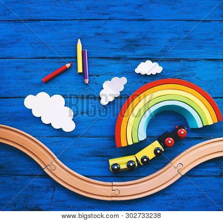 Wooden Toy Train, Railway For Preschool Child, Wood Rainbow, Colored Pencils On Blue Table. Daycare,