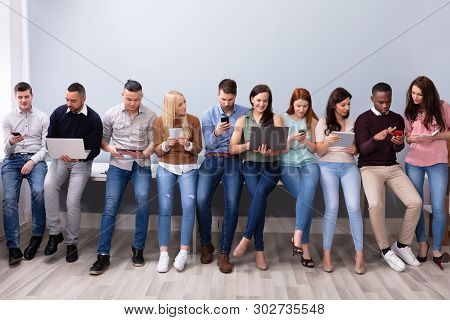 Multiracial Millennial People In Row Busy In Using Modern Electronic Gadgets