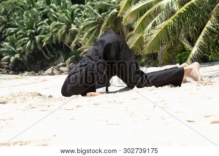 Side View Of Unsuccessful Businessman Burying His Head In The Sand At Beach