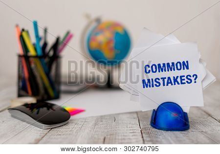 Handwriting text Common Mistakes question. Concept meaning repeat act or judgement misguided or wrong Stationary and computer stuffs with artificial globe on the wooden desk. poster