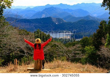Woman looking over the mountain landscape with the Oyunohara torii gate, the tallest in the word, Japan