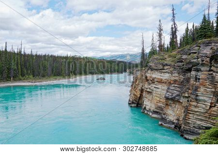 Turquoise River Athabasca Flowing Down From The Glaciers At Summer. The River Goes Around Picturesqu