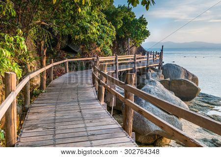 Scenic sea coastline of the Phangan island in Thailand with wooden path along the rocky shore