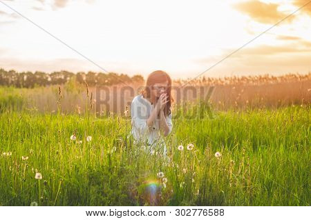 Girl Closed Her Eyes, Praying In A Field During Beautiful Sunset. Hands Folded In Prayer Concept For