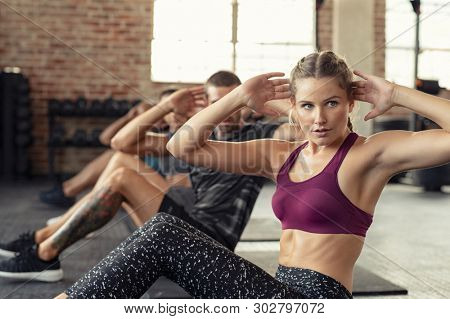 Young fitness woman doing abdominal exercise at gym. Concentrated people in a row doing sit ups on yoga mat. Training class doing situps at fit center.