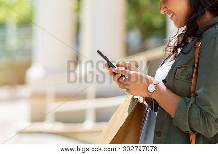 Closeup of woman hands holding shopping bags and using smartphone outdoor. Shopaholic girl checking online with smart phone shopping deals. Young stylish woman using mobile phone for ecommerce.
