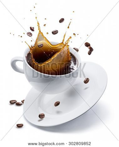 Splash of coffee in white cup and coffee beans in air. Isolated on white.