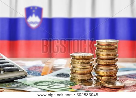 Euro Banknotes And Coins In Front Of The National Flag Of Slovenia