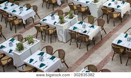 Top View On An Empty Restaurant. Tables Are Covered With White Tablecloths. Brown Wicker Chairs. Gre