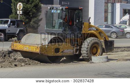 Kazakhstan, Ust-kamenogorsk, April 23, 2019: Steamroller Performing Leveling Work On A Road Under Co