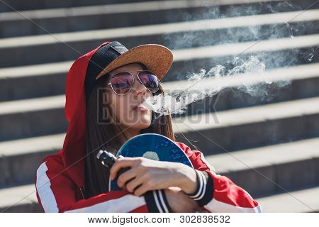 Vaping Girl. Young Woman With Skateboard Vape E-cig. Pretty Young Female In Black Hat, Red Clothing
