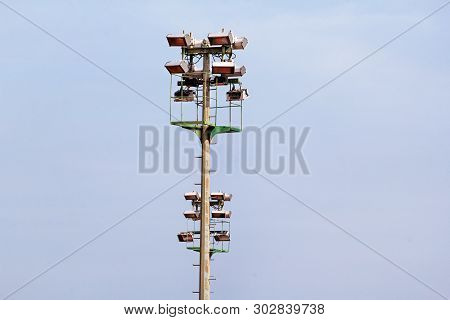Stadium Floodlight Tower With Reflectors With Blue Sky. Lighting Pole Tower At The Sports Stadium An