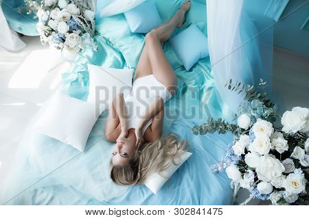 Boudoir Photography. Woman Blonde With Long Hair In Lingerie On The Bed Surrounded By Flowers Tulips