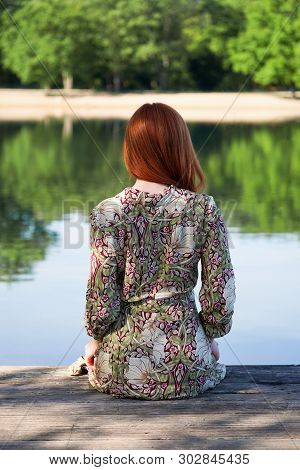 Back View Of Young Woman Wearing Summer Dress And Sitting On Wooden Pier Looking At Idyllic Lake