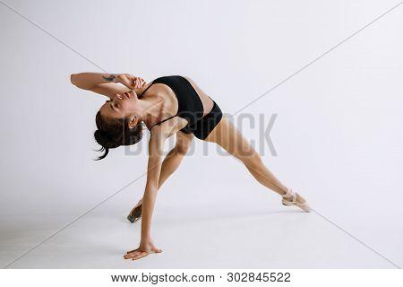 Fashion Ballet. Young Female Ballet Dancer In Black Bodysuit Against White Studio Background. Caucas