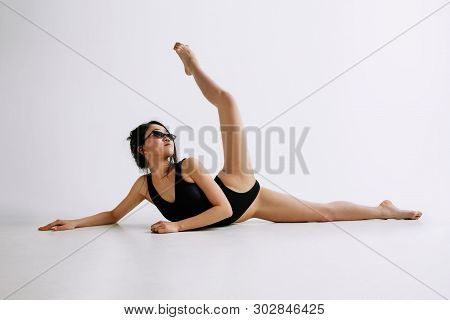 Fashion Ballet. Young Female Ballet Dancer In Black Bodysuit Against White Studio Background. Asian