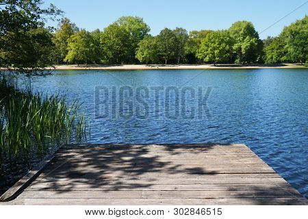 Empty Wooden Pier Or Jetty Overlooking Bathing Lake - Idyllic Nature Background With Copy Space