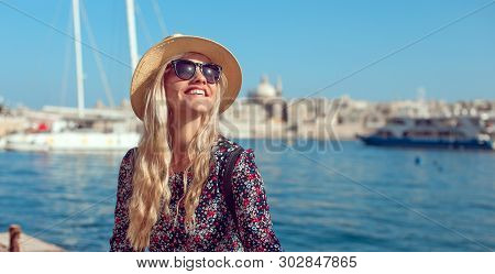 Happy Blonde Tourist Lady In Hat Enjoying Mediterranean City At Sea And Sunshine