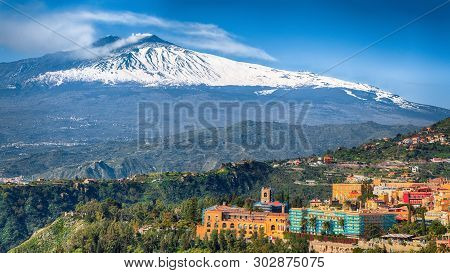 Etna Volcano And Taormina Town Aerial Panoramic View. Roofs Of A Lot Of Buldings. Smoking Snow-cappe