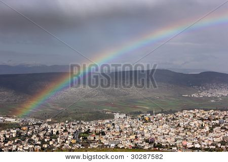 rainbow over the Arab village of Cana in the Galilee region of Israel. poster