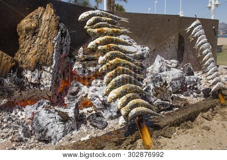 Grilling Espetos At Malaga Chiringuito, Spain. Espetos Are Skewer With Sardines In A Fire Typical Fo