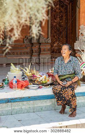 Dusun Ambengan, Bali, Indonesia - February 25, 2019: Closeup Of Woman Sitting Op Open Patio With Sel