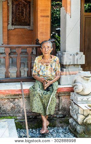 Dusun Ambengan, Bali, Indonesia - February 25, 2019: Family Compound. Closeup Of Older Lady Sitting