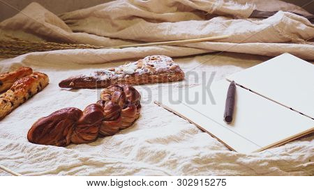 Breads And Toast For Breakfast And Note Book On White Bed Sheet Background, Healthy Breakfast. Morni