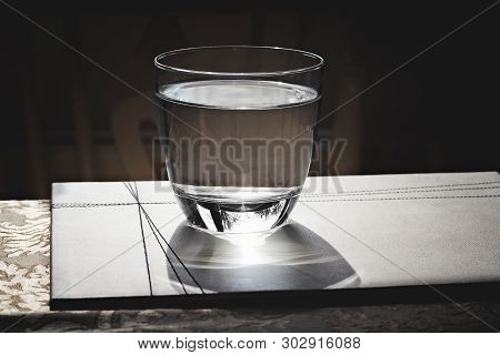 Glass Of Water On The Table With Reflections On It. Close View.