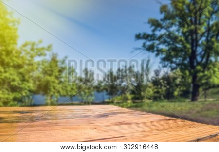 Empty Wooden Deck Table With Park Blur Background.