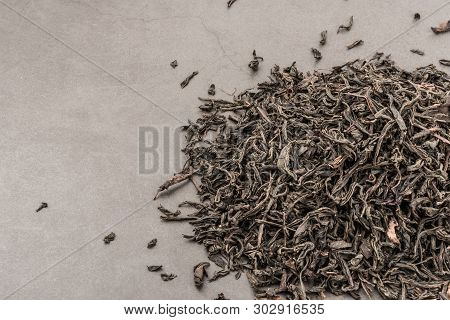 Dried Tea Is Poured Scattered On A Grey Textured Background.