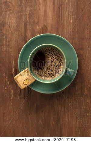 A Cup Of Black Coffee With A Cookie On A Dark Rustic Wooden Background, Shot From Above With A Place