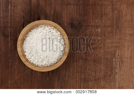 A Bowl Of Coarse Sea Salt, Shot From Above On A Dark Rustic Wooden Background With A Place For Text