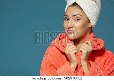 Portrait of young woman during morning procedures. Charming teen girl with towel on her head wearing bathrobe looking at camera like at mirror, isolated over blue background